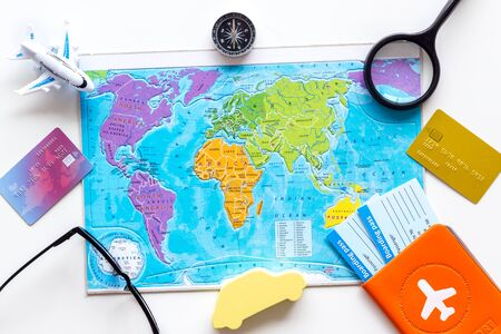 Planning a travel concept. Map of the world and tourist accessories on white background top view