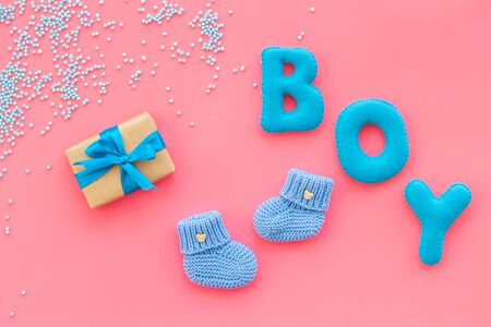 Childrens birthday concept. Word boy near booties and present box on pink background top view