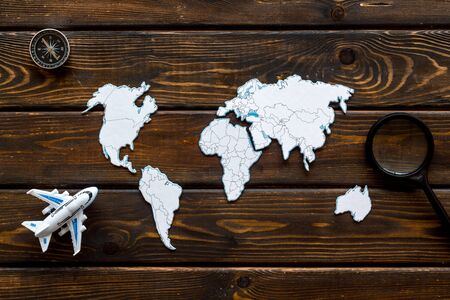Planning a travel concept. Sketchy map of the world on dark wooden background top view