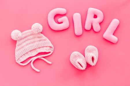 Decoration for babys birthday. Word girl near booties on pink background top view Stock Photo