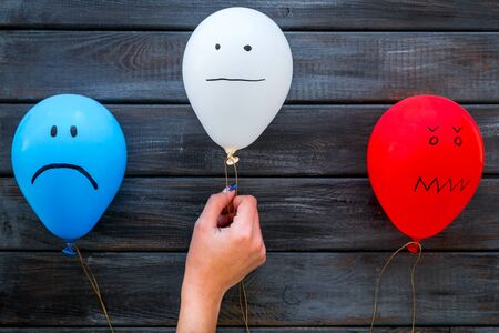 Negative emotions concept. Balloons with drawn faces on dark wooden background top view.