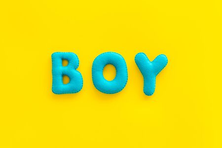 Boy word as decoration for baby shower on yellow background top view Stock Photo