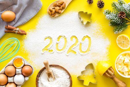 Frohes neues Jahr-Konzept. 2020 geschrieben auf Draufsicht des gelben Backenhintergrundes