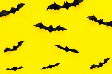 Halloween background with bats on yellow table top view