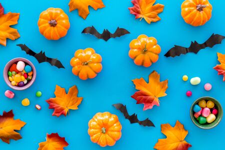 Bright Halloween composition with sweets, bats and pumpkins on blue background top view pattern