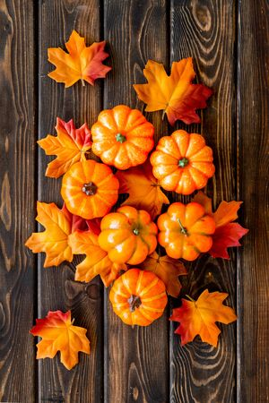 Autumn composition with red and orange leaves and pumpkins on dark wooden background top view