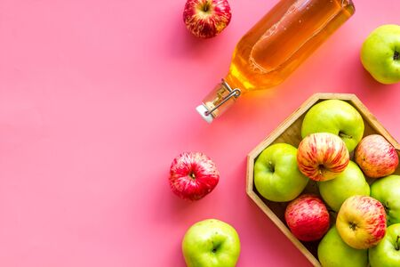 Apple cider in bottle near tray with fruits on pink background top view.