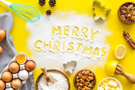 Merry Christmas written on yellow baking background top view