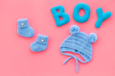 Childrens birthday concept. Word boy near booties on pink background top view