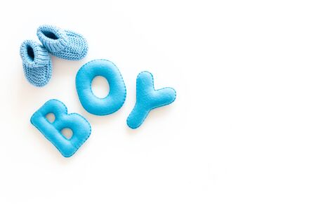 Childrens birthday concept. Word boy near booties on white background top view frame copy space