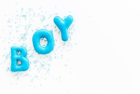 Boy word as decoration for baby shower on white background top view copy space