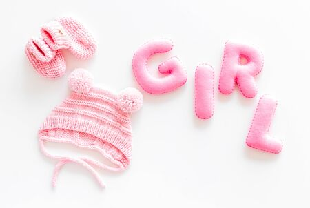 Decoration for babys birthday. Word girl near booties on white background top view