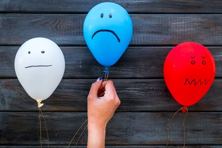 Negative emotions concept. Balloons with drawn faces on dark wooden background top view Banco de Imagens