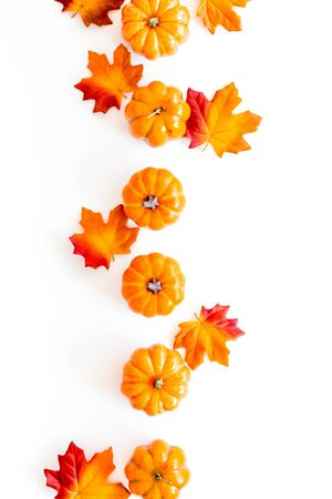 Autumn composition. Pattern with red and orange leaves and pumpkins on white background top view copy space