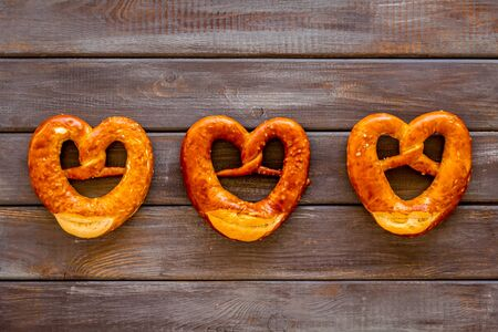 Octoberfest symbol. Fresh bavarian pretzels on dark wooden background top view Stock Photo