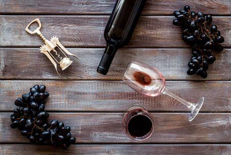 Red wine bottle near wineglass on darkw background top view Фото со стока