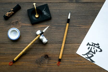 Chinese or japanese hieroglyph in translation in english means Love. Calligraphy concept. Wooden background top view Stockfoto