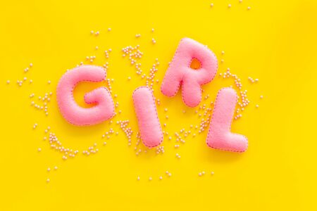 Girl word as decoration for baby shower on yellow background top view Stock Photo