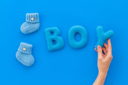 Childrens birthday concept. Word boy near booties on blue background top view