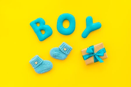 Childrens birthday concept. Word boy near booties and present box on yellow background top view Stockfoto