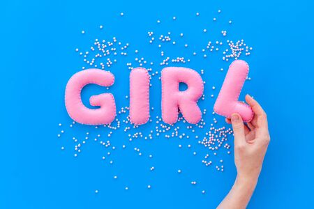 Girl word as decoration for baby shower on blue background top view