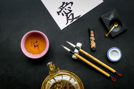 Chinese or japanese hieroglyph in translation in english means Love. Calligraphy concept. Black background top view