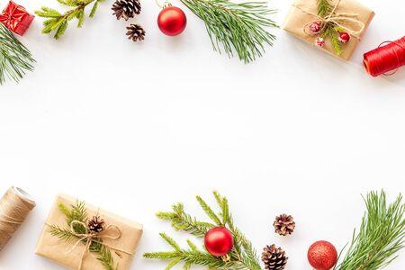 Cornice di Capodanno con rami di abete e modello di scatola regalo su sfondo bianco vista dall'alto spazio copia