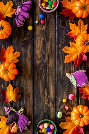 Nice halloween background with sweets. Cookies and pumpkins on dark wooden top view frame copy space Kho ảnh