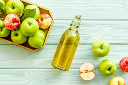 Vinegar made from fresh apple on green wooden background top view space for text