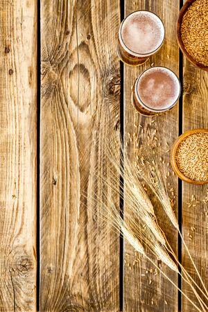 Beer ingredients. Barley near beer glasses on rustic wooden background top view copy space