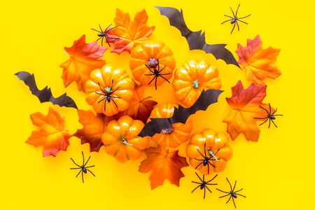Halloween composition with pumpkins, spiders and bats on yellow background top view 写真素材