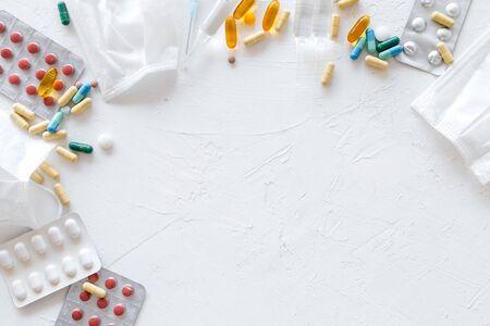 Trate la gripe y el concepto de resfriado. Vacuna, mascarilla, píldoras sobre fondo blanco espacio de copia de marco de vista superior Foto de archivo