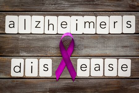 Alzheimers disease text near violet ribbon on dark wooden background top view