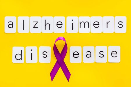 Alzheimers disease text near violet ribbon on yellow background top view Stock Photo