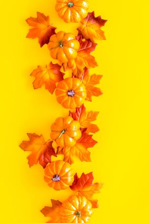 Autumn composition. Pattern with red and orange leaves and pumpkins on yellow background top view