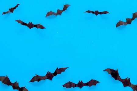 Bats cutout on Halloween frame on blue table top view copy space