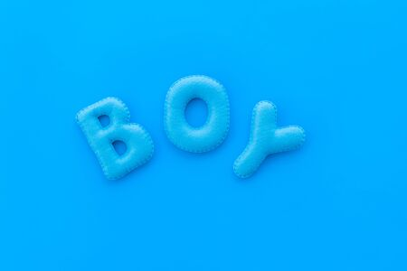 Boy word as decoration for baby shower on blue background top view Stock Photo