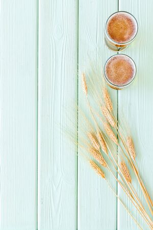 Barley or wheat as beer ingredient near beer glasses on green wooden background top view copy space