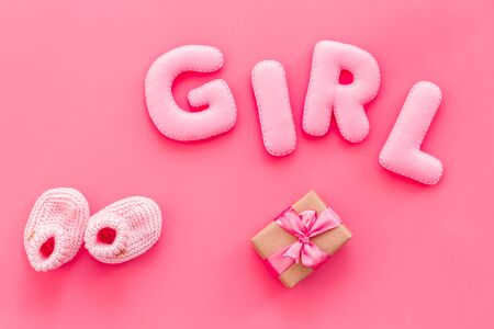 Decoration for babys birthday. Word girl near booties and present box on pink background top view Stock Photo