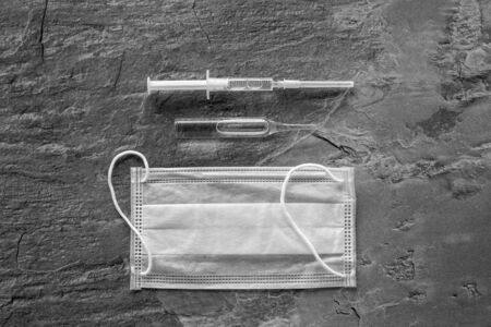 Influenza preventive tools. Medical face mask and vaccine on grey background top view copy space Reklamní fotografie - 130741124