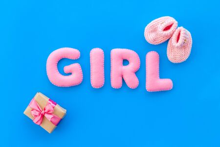 Decoration for babys birthday. Word girl near booties on blue background top view Archivio Fotografico - 130741172