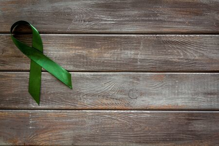 Green ribbon as symbol of disease control on dark wooden background top view space for text