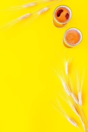 Barley or wheat as beer ingredient near beer glasses on yellow background top view copy space Stock Photo