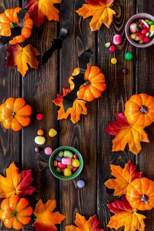 Bright Halloween composition with sweets, bats and pumpkins on dark wooden background top view pattern