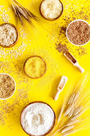 Healthy food concept. Cereals in bowls on yellow background top view