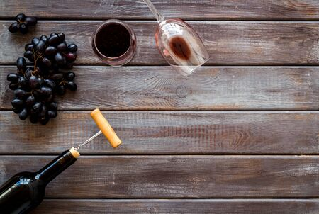 Red wine bottle near wineglass on dark wooden background top view copy space