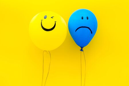 Treat depression concept. Balloons with sad and smiling faces on yellow background top view.