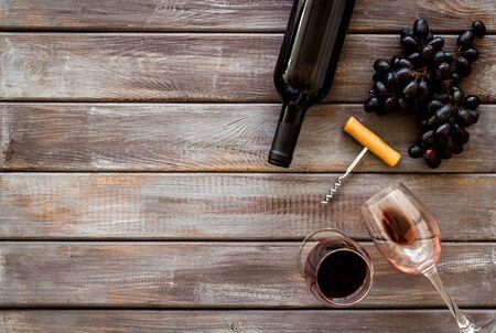 Testing wine concept. Wine bottle near black grape, wineglass and corkscrew Фото со стока - 130747311
