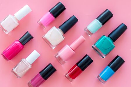 Nail polishes background on pink table top view pattern