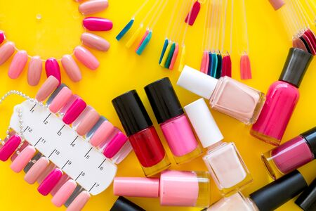 Ð¡hoose nail polish. Polishes and color samples on yellow background top view Stok Fotoğraf
